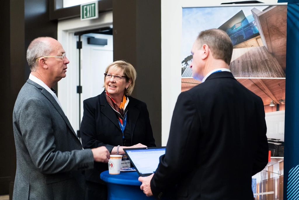 3 colleagues networking at a conference